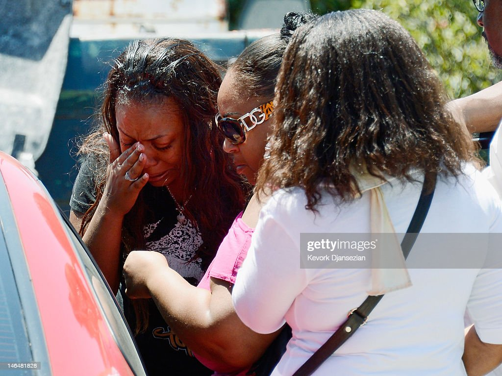 Lora (L) and Candice (C), daughters of Rodney King, cry after their father was found in bottom of his pool on June 17, 2012 in Rialto, California. King, whose video beating by Los Angeles police in 1991 sparked riots after the acquittal of the four officers involved, was found dead at the age of 47 from an apparent drowning in his swimming pool.