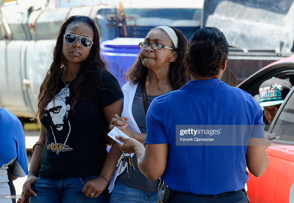 Lora King (L), daughter of Rodney King, is comforted by a relative as detective Carla McCulloiugh speaks to them on June 17, 2012 in Rialto, California. King, whose video beating by Los Angeles police in 1991 sparked riots after the acquittal of the four officers involved, was found dead at the age of 47 from an apparent drowning in his swimming pool.