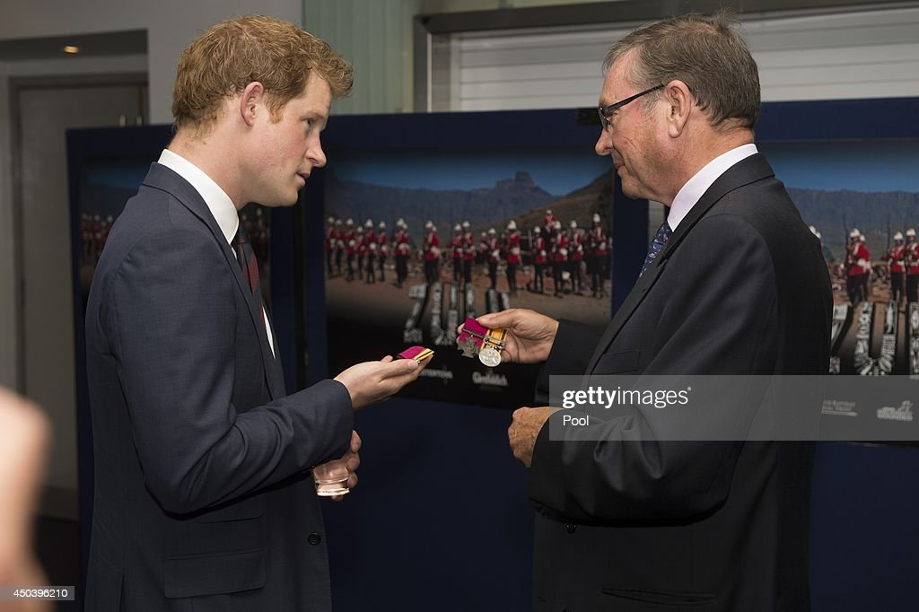 Lord Ashcroft shows Prince Harry some medals awarded for bravery during the battle at Rorke's Drift during the 50th anniversary screening of Zulu at Odeon Leicester Square on June 10, 2014 in London, England.
