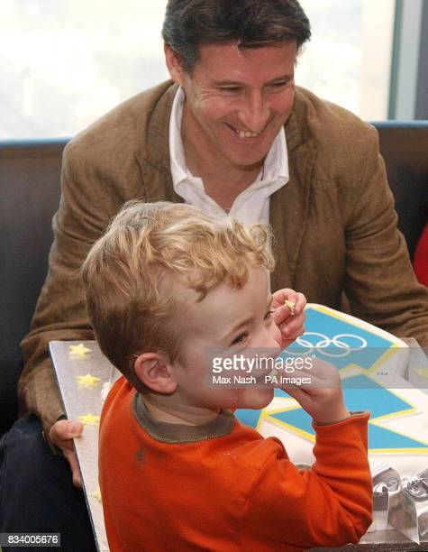 Lord Coe watches as William Talbot uninvitedly helps himself to a piece of his birthday cake at an event with children celebrating their third...
