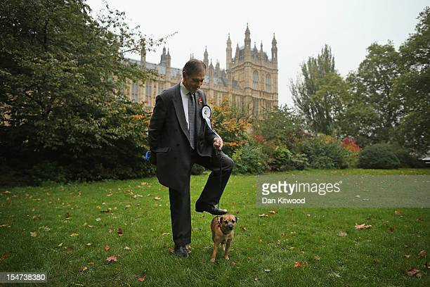 Lord Flight stands in front of The Houses of Parliament with his dog Doris a Border Terrier during the Westminster Dog of The Year competition in...