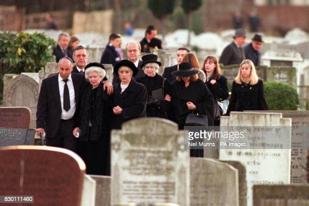 Lord Grade's widow Kathleen is comforted by mourners in Willesden Liberal Cemetery today December 1998 following the funeral of her husband TV...