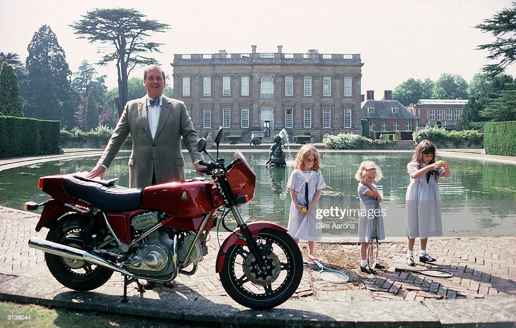Lord Hesketh, Minister of State at the Department of Trade and Industry, by the lake in the grounds of his family estate Easton Neston House, Northamptonshire with his motorbike, a Hesketh V1000. The child in the centre is his daughter, Sophie.