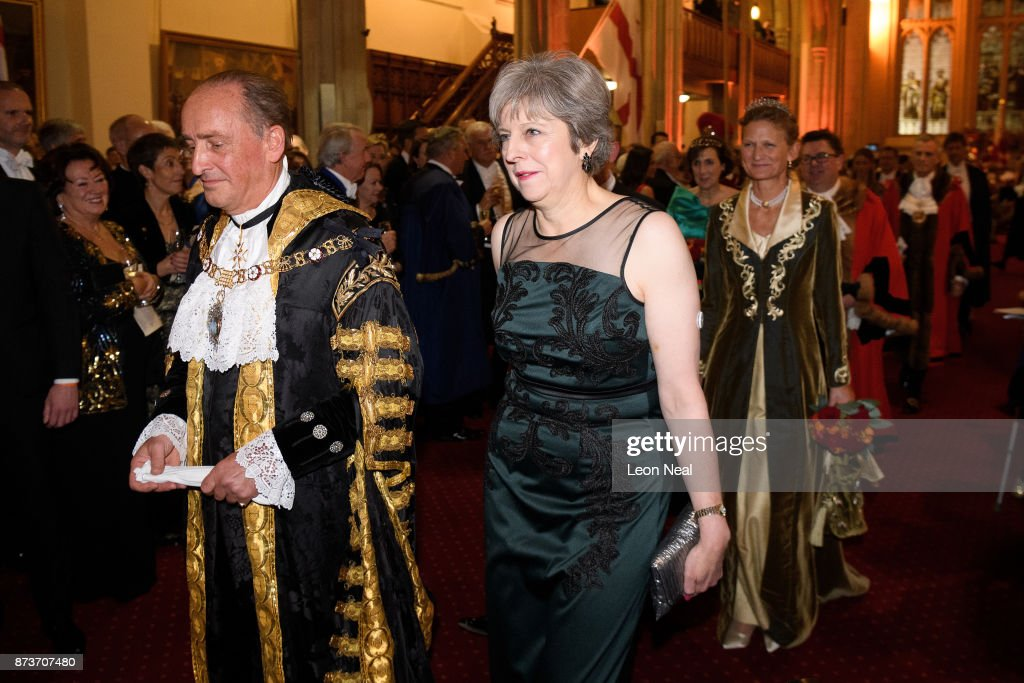 Lord Mayor of London Charles Bowman and Britain's Prime Minister Theresa May attend the annual Lord Mayor's banquet on November 13, 2017 in London, England. The Prime Minister will address dignitaries and special guests after a formal meal. The British Prime Minister Theresa May, long known to have Type 1 Diabetes, has been wearing a Nootrobox Continuous Glucouse Monitoring (CGM) patch on her upper arm to help with the control of the disease. The CGM device is implanted into the skin and sends data on glucose levels to a smart phone. Last night the implant was seen clearly on the Prime Minister's arm as she wore a sleeveless, green evening dress.