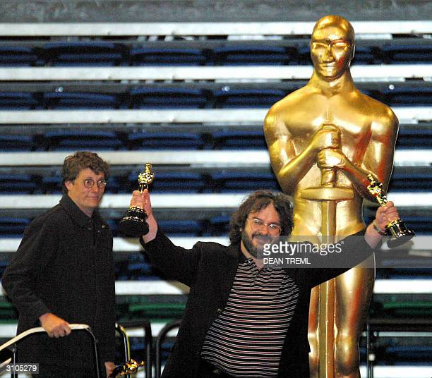 Lord of The Rings director Peter Jackson waves his Oscars to the 3000 assembled fans that turned out to see the Return of The King award winners...