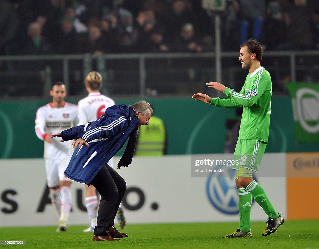 Lorenz - Guenther Koestner, head coach of Wolfsburg celebrates with winning goal scorer <a gi-track='captionPersonalityLinkClicked' href=/galleries/search?phrase=Bas+Dost&family=editorial&specificpeople=7467816 ng-click='$event.stopPropagation()'>Bas Dost</a> at the end of the round of 16 of the DFB cup match between VfL Wolfsburg and Bayer Leverkusen at Volkswagen Arena on December 19, 2012 in Wolfsburg, Germany.