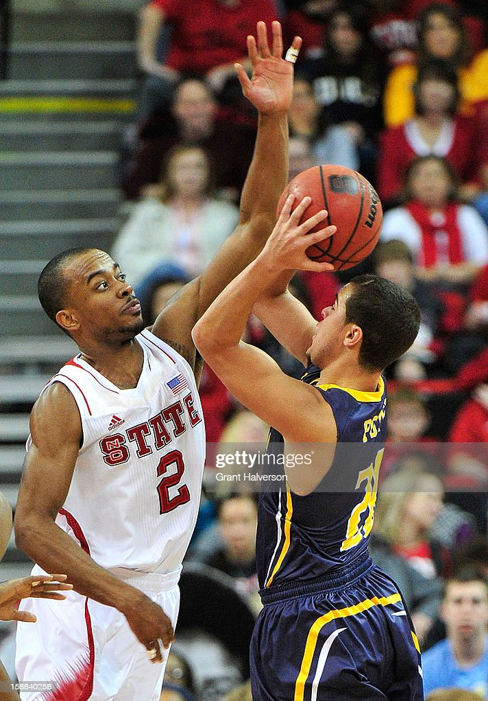 Lorenzo Brown #2 of the North Carolina State Wolfpack challenges a shot by Jordan Potts #20 of the UNC Greensboro Spartans during play at PNC Arena on December 31, 2012 in Raleigh, North Carolina. North Carolina State won 89-68.