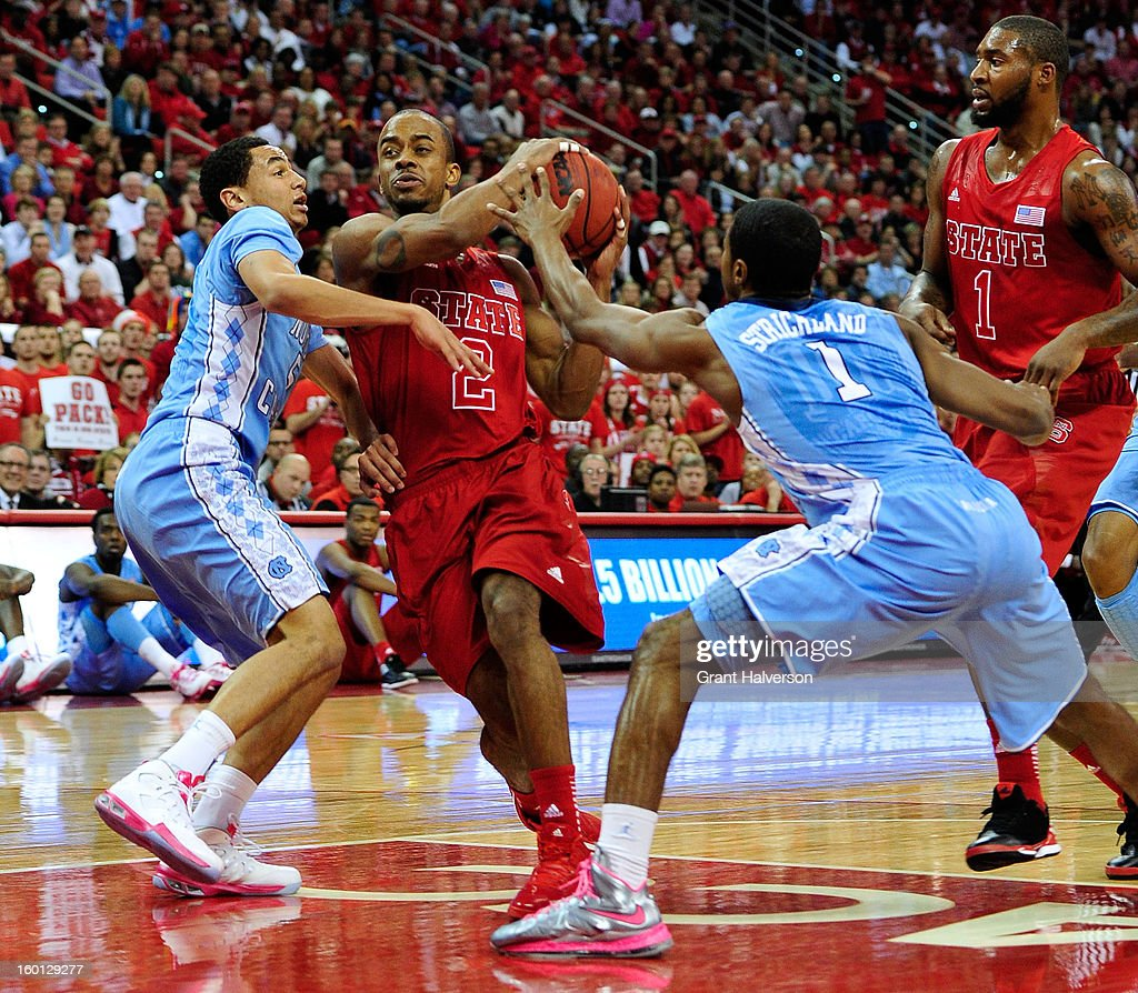 Lorenzo Brown #2 of the North Carolina State Wolfpack drives between Marcus Paige #5 and <a gi-track='captionPersonalityLinkClicked' href=/galleries/search?phrase=Dexter+Strickland&family=editorial&specificpeople=5792010 ng-click='$event.stopPropagation()'>Dexter Strickland</a> #1 of the North Carolina Tar Heels during play at PNC Arena on January 26, 2013 in Raleigh, North Carolina.