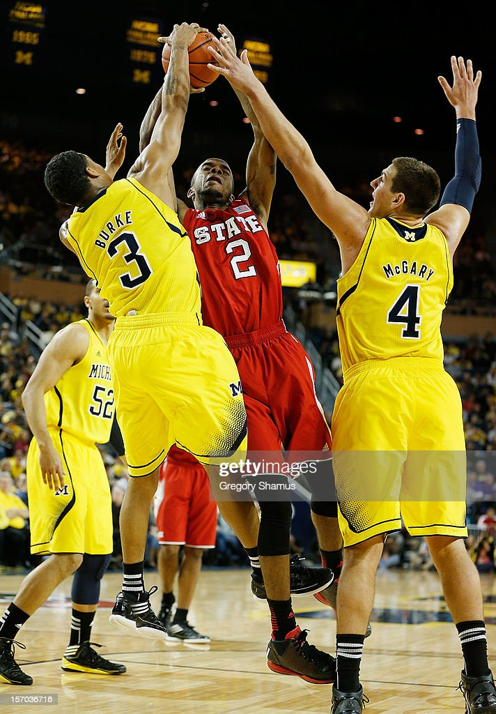Lorenzo Brown #2 of the North Carolina State Wolfpack gets a second half shot blocked by Trey Burke #3 and Mitch McGary #4 of the Michigan Wolverines at Crisler Center on November 27, 2012 in Ann Arbor, Michigan. Michigan won the game 79-72.
