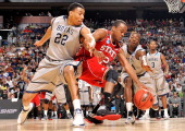 Lorenzo Brown of the North Carolina State Wolfpack goes for a loose ball against Otto Porter and Jason Clark of the Georgetown Hoyas in the first...