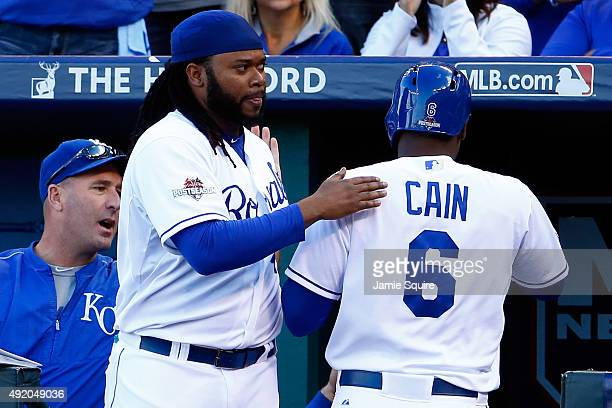 Lorenzo Cain of the Kansas City Royals celebrates with his teammate Johnny Cueto after scoring a run off of single hit by Eric Hosmer in the sixth...