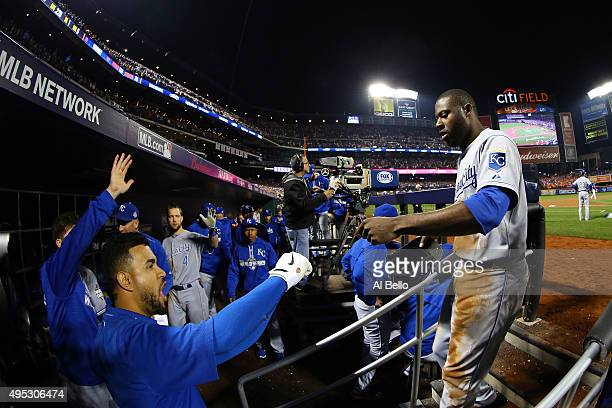 Lorenzo Cain of the Kansas City Royals celebrates with his teammates in the dugout after scoring a run off of a double hit by Eric Hosmer of the...