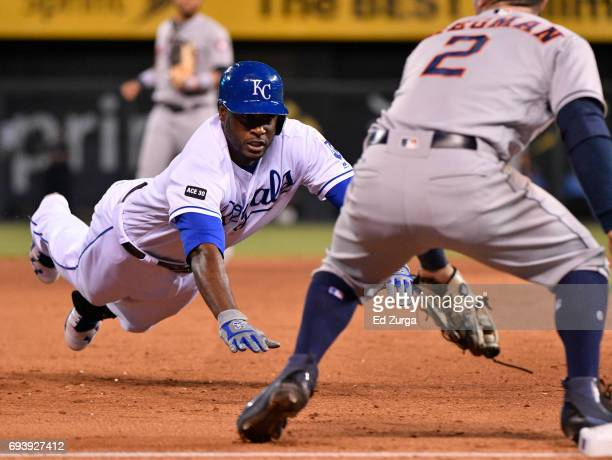 Lorenzo Cain of the Kansas City Royals dives into third for a triple past Alex Bregman of the Houston Astros in the seventh inning at Kauffman...