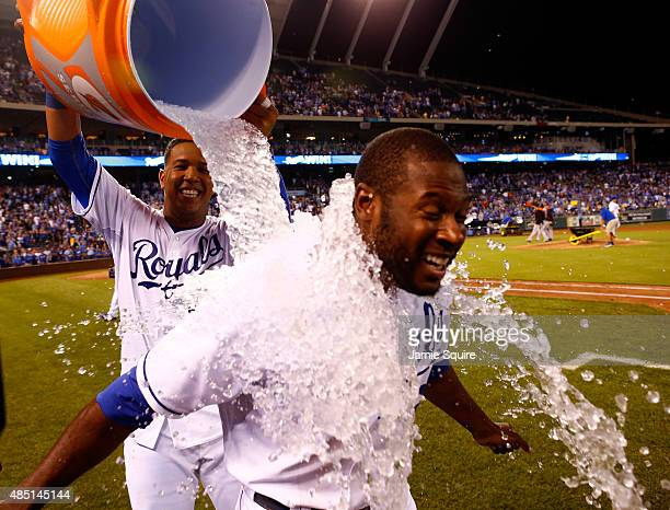 Lorenzo Cain of the Kansas City Royals is doused with water by Salvador Perez after the Royals defeated the Baltimore Orioles 83 to win the game at...