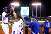 Lorenzo Cain of the Kansas City Royals is greeted by Kendrys Morales of the Kansas City Royals at the dugout after scoring a run on an RBI single hit...