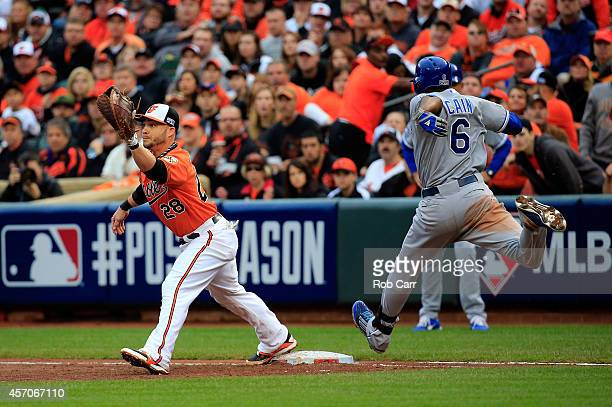 Lorenzo Cain of the Kansas City Royals reaches first base against Steve Pearce of the Baltimore Orioles on an infield single in the third inning...