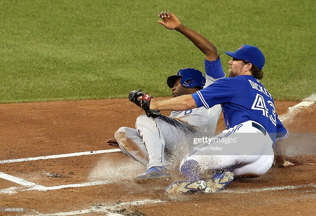<a gi-track='captionPersonalityLinkClicked' href=/galleries/search?phrase=Lorenzo+Cain&family=editorial&specificpeople=5746615 ng-click='$event.stopPropagation()'>Lorenzo Cain</a> #6 of the Kansas City Royals scores a run in the first inning as <a gi-track='captionPersonalityLinkClicked' href=/galleries/search?phrase=R.A.+Dickey&family=editorial&specificpeople=221719 ng-click='$event.stopPropagation()'>R.A. Dickey</a> #43 of the Toronto Blue Jays attempts to make the tag during game four of the American League Championship Series at Rogers Centre on October 20, 2015 in Toronto, Canada.