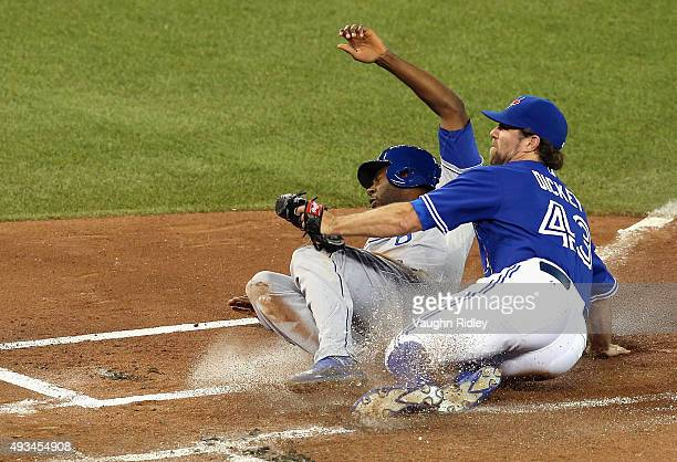 Lorenzo Cain of the Kansas City Royals scores a run in the first inning as RA Dickey of the Toronto Blue Jays attempts to make the tag during game...