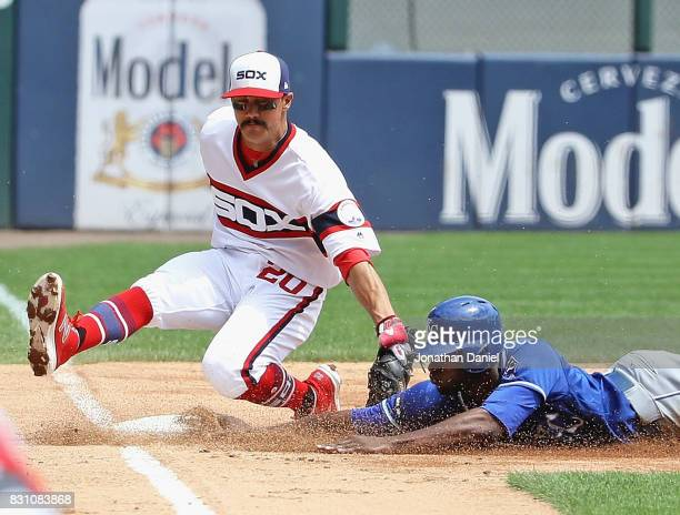 Lorenzo Cain of the Kansas City Royals slides safely into third base on a wild pitch as Tyler Saladino of the Chicago White Sox is late with the tag...