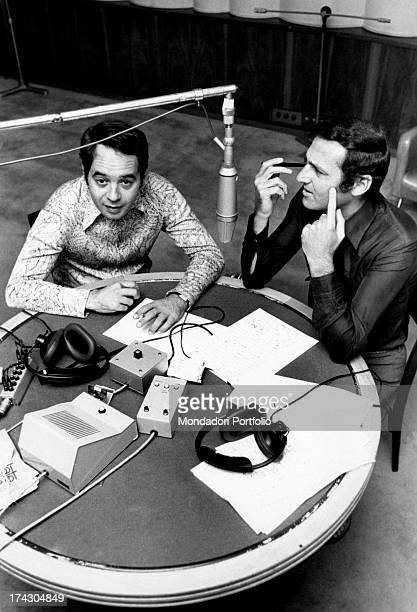 Lorenzo John Arbore known as Renzo Arbore and Gianni Boncompagni are sitting in a room of a recording studio with microphones headphones and the...