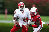 Lorenzo Mauldin of the Louisville Cardinals grabs onto Jacoby Brissett of the North Carolina State Wolfpack during the game at Papa John's Cardinal...