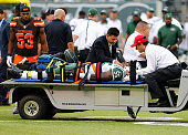 Lorenzo Mauldin of the New York Jets is carted off the field on a stretcher as Craig Robertson of the Cleveland Browns looks on during the fourth...