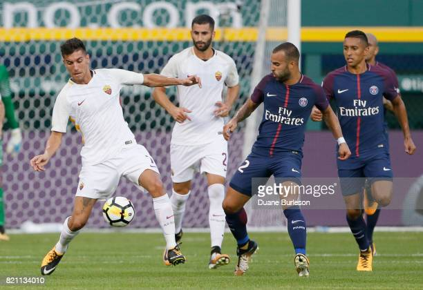 Lorenzo Pellegrini of AS Roma is controls the ball against Jese of Paris SaintGermain as Leandro Castan of AS Roma watches during the first half at...