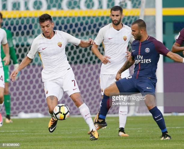 Lorenzo Pellegrini of AS Roma steals the ball from Jese of Paris SaintGermain as Leandro Castan of AS Roma follows the play during the first half at...
