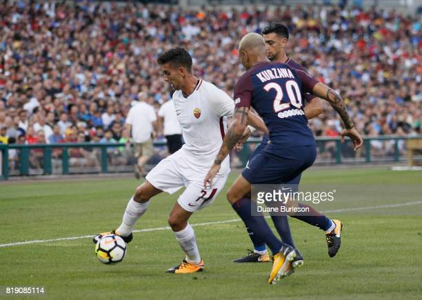 Lorenzo Pellegrini of AS Roma tries to maintain control off the ball against Layvin Kurzawa of Paris SaintGermain and Javier Pastore of Paris...