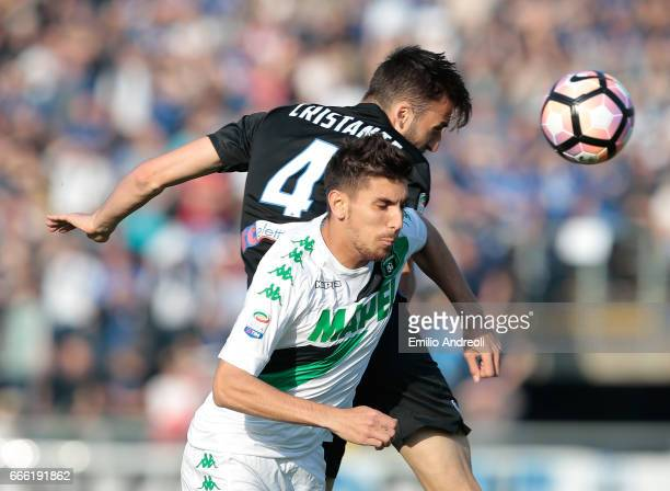 Lorenzo Pellegrini of US Sassuolo Calcio jumps for the ball with Bryan Cristante of Atalanta BC during the Serie A match between Atalanta BC and US...