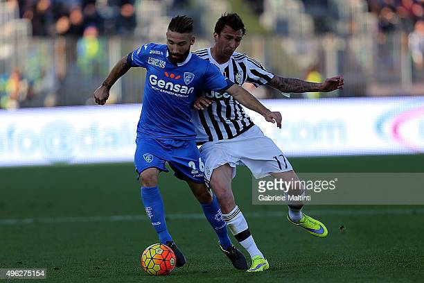 Lorenzo Tonelli of Empoli FC battles for the ball with Mario Mandzukic of Juventus FC during the Serie A match between Empoli FC and Juventus FC at...