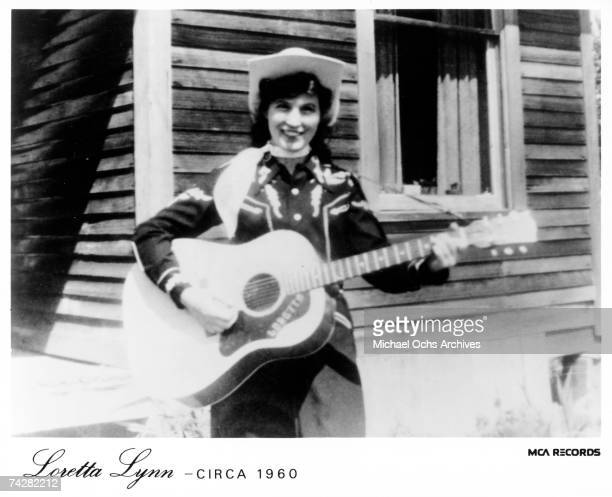 Loretta Lynn holds her acoustic guitar as she poses for a portrait wearing a cowboy hat a scarf and western shirt outside a log cabin in circa 1960