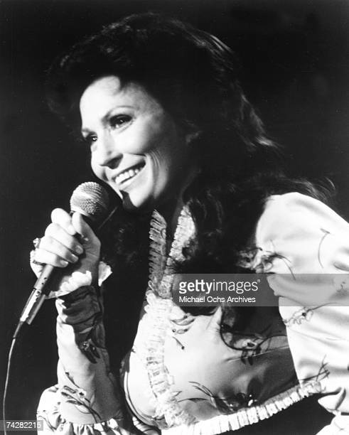 Loretta Lynn performs onstage with a microphone in circa 1975
