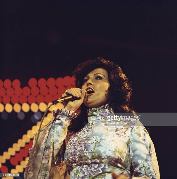 Loretta Lynn US country music singersongwriter singing into a microphone during a concert circa 1970