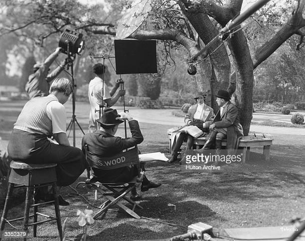 Loretta Young and Roland Young being directed by Sam Wood in a park scene from the MGM film 'The Unguarded Hour'