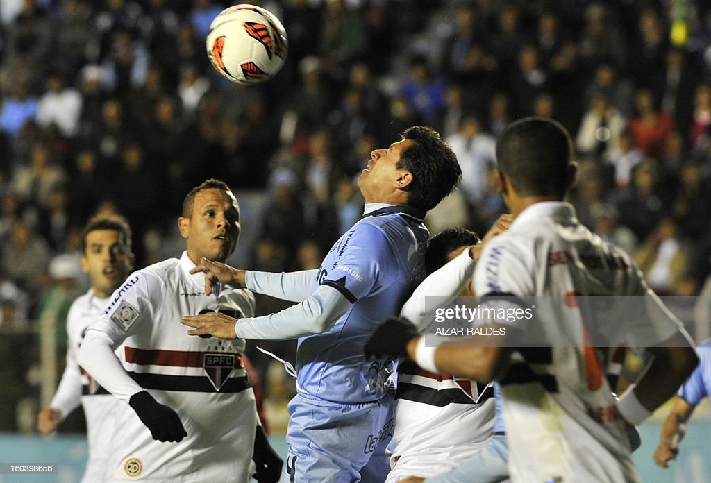 Lorgio Alvarez (C) of Bolivia's Bolivar, heads the ball marked by Luis Fabiano (L) of Brazil's Sao Paulo , during a Copa Libertadores football match at the Hernando Siles stadium in La Paz, Bolivia, on January 30, 2013.AFP PHOTO / Aizar Raldes