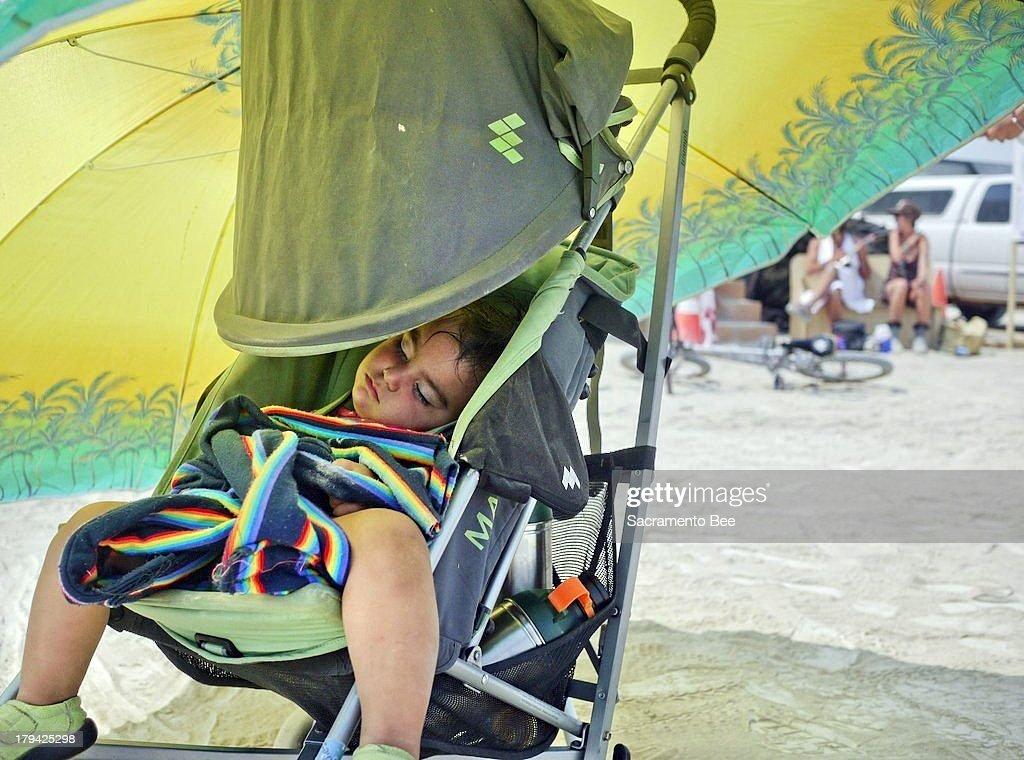 Lori Pirone and her partner Alejando Otero use an oversized umbrella to shade their 18-month-old from the sun August 26, 2013 at Burning Man. Burning Man, which concluded Labor Day and drew more than 60,000 people from across the globe to Nevada's Black Rock Desert, celebrates music, art and independent thinking in communal, free-spirited environment.