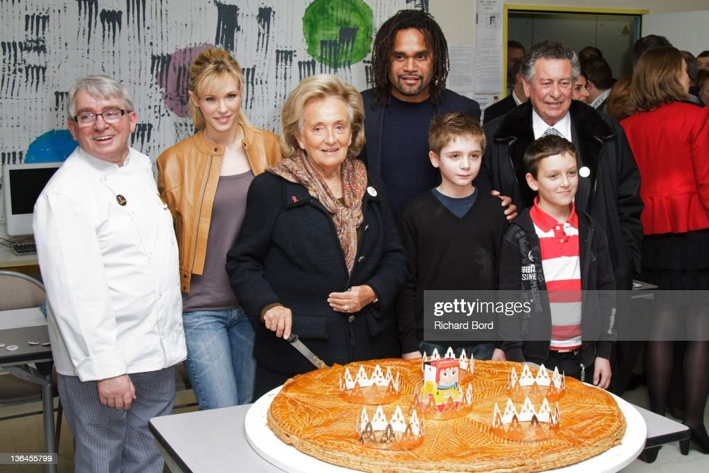 Lorie Baker Remy Potey Bernadette Chirac Christian Karambeu and children pose with a 'Galette des Rois' during the 'Pieces Jaunes' 23rd Campaign...