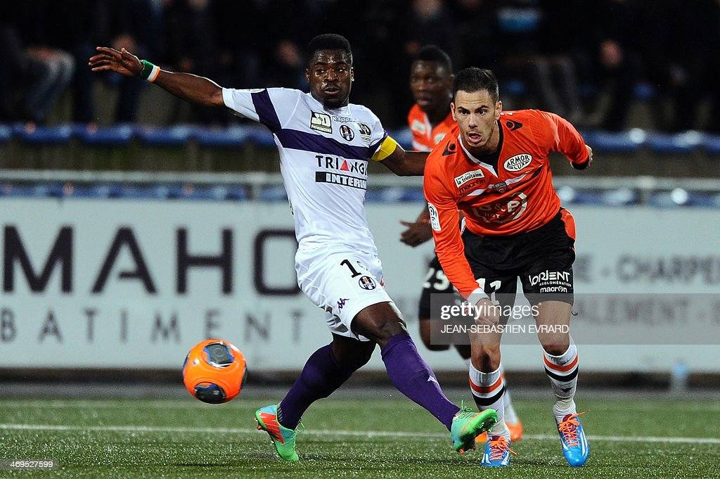 Lorient French forward Jeremie Aliadiere (R) vies with Toulouse's French defender Serge Aurier during the French L1 football match between Lorient and Toulouse on February 15, 2014 at the Moustoir stadium in Lorient, western France. AFP PHOTO / JEAN-SEBASTIEN EVRARD