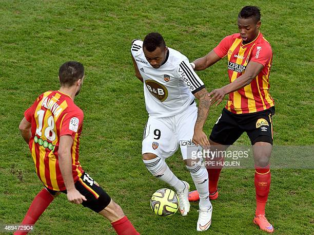 Lorient's Cameroonian forward Vincent Aboubakar vies for the ball with Lens' French midfielder Wylan Cyprien and Lens' French midfielder Pierrick...