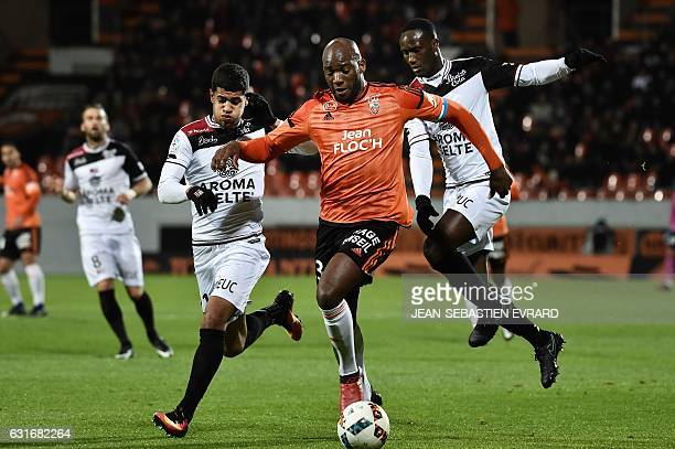 Lorient's French defender Michael Ciani vies with Guingamp's French midfielder Ludovic Blas and Guingamp's Ivorian defender Brou Benjamin Angoua...