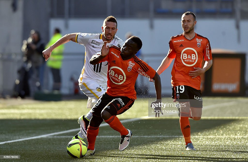 Lorient's French defender Pape Abdou Paye (C) vies for the ball with Lille's French midfielder Morgan Amalfitano (L) during the French L1 football match between Lorient (FCL) and Lyon (OL) at the Moustoir Stadium in Lorient, western France, on April 30, 2016.