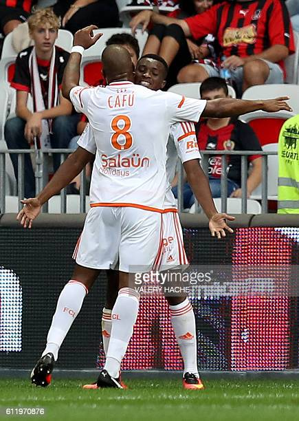 Lorient's French forward Benjamin Moukandjo celebrates after scoring a goal with Lorient's Portuguese midfielder Carlos Miguel Cafu during the French...