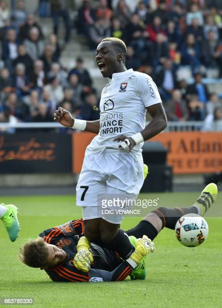Lorient's French goalkeeper Benjamin Lecomte vies with Caen's French forward Yann Karamoh during the French L1 football match Lorient vs Caen at the...