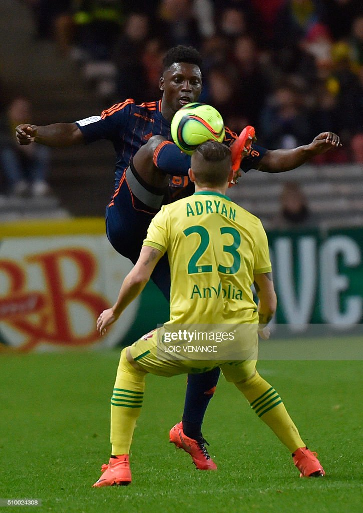 Lorient's French Senegalese defender Lamine Gassama (L) vies with Nantes' Brazilian midfielder Adryan Oliveira Tavares during the French L1 football match Nantes vs Lorient, at the la Beaujoire stadium in Nantes, western France, on February 13, 2016. AFP PHOTO / LOIC VENANCE / AFP / LOIC VENANCE