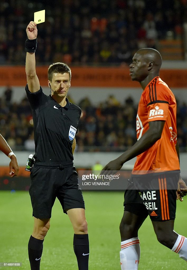 Lorient's Senegalese defender Zargo Toure is shown a yellow card by French referee Benoit Bastien during the French L1 football match Lorient vs Nantes, at the Moustoir Stadium in Lorient, western France, on October 15, 2016. / AFP / LOIC