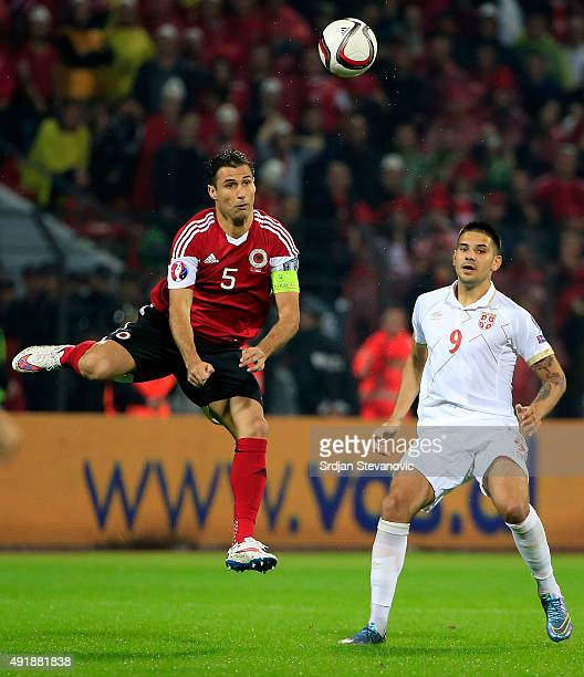 Lorik Cana of Albania jump for the ball against Aleksandar Mitrovic of Serbia during the Euro 2016 qualifying football match between Albania and...