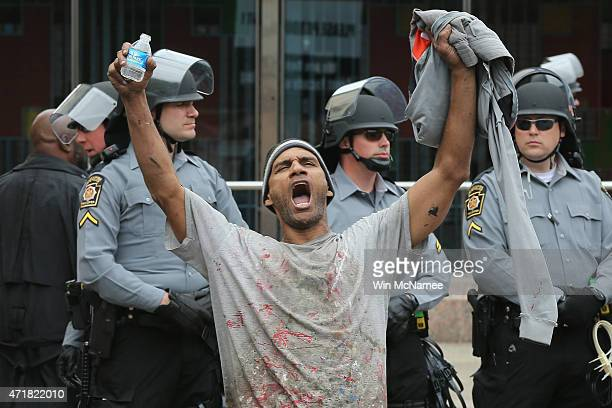 Lorning Cornish shouts after Baltimore authorities released a report on the death of Freddie Gray while police in riot gear stand guard on May 1 2015...