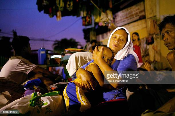 Lornitas Calub hugs her grandson at a crowded evacuation shelter August 13 2012 in Manila Philippines The weather is slated to deteriorate as another...