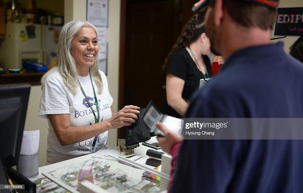 Lorraine Cendejas of Botana Care, left, helps customers purchasing recreational marijuana. Northglenn, Colorado. May 16. 2014.